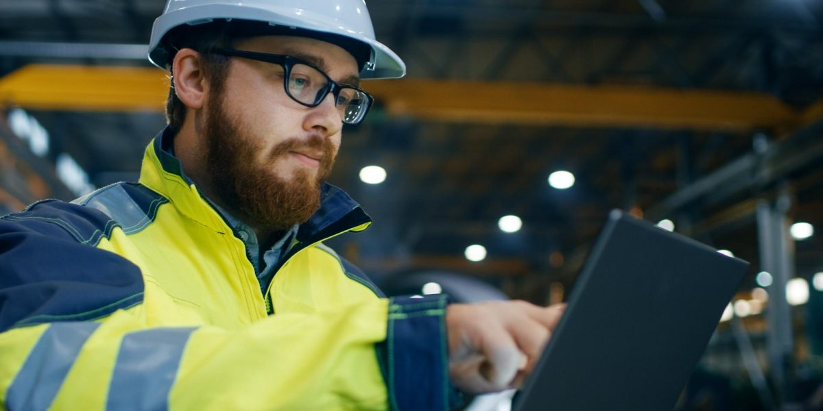 man with glasses in safety jacket with laptop